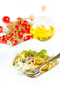 Italian pasta with fresh basil, olive oil and tomatoes — Stock Photo