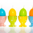 Multicolored easter eggs candles in eggcups — Stock Photo #13403904