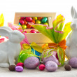 Assorted eggs and bunnies on white — Stock Photo