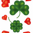 Four leaf clover and red hearts — Stock Photo