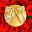 Red roses and golden gift box with ribbon — Stock Photo