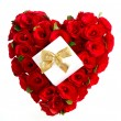 Heart of red roses with gift and golden bow — Stock Photo