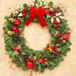 Christmas wreath with red ribbon on golden wallpaper — Stock Photo