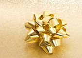 Beautiful bow on shiny golden background — Stock Photo