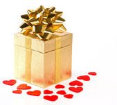 Golden gift box with bow and red hearts decoration — Stock Photo