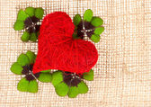 Red heart and fresh green clover leaves — Stock Photo