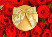 Red roses and golden gift box with ribbon — Stockfoto