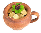 Old ceramic pot with money coins and clover leaf on white background — Stock Photo