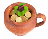 Old ceramic pot with money coins and clover leaf — Stock Photo