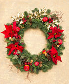 Christmas wreath with red poinsettia flowers — Stock Photo