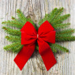 Christmas fir tree with red ribbon on the wooden background — Stock Photo