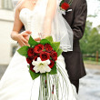 Bride holding beautiful red roses. wedding flowers bouquet — Stock Photo #13411680