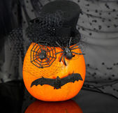 Funny pumpkin with spiders and bat on black — Stock Photo