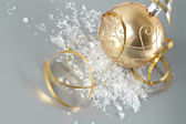 Golden christmas ball with golden streamer — Stock Photo