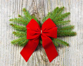 Christmas fir tree with red ribbon on the wooden background — Photo