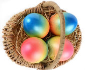 Colorful painted easter eggs in brown basket — Photo