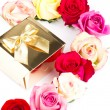 Multicolor roses and golden gift on white — Stock Photo