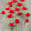 Petals of red rose over wooden background — Stock Photo #13429568