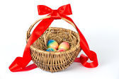 Colorful painted easter eggs in brown basket — Stockfoto