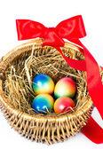 Barevné malování velikonočních vajíček, hnědý koš s červenou stužku — Stock fotografie