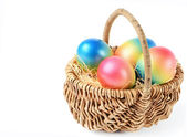 Colorful painted easter eggs in brown basket — Stock Photo