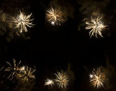 Beautiful golden fireworks exploding over a dark night sky — Stock Photo