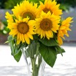 Sunflowers in a transparent glass vase on nature background — Stock Photo
