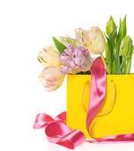 Fresh spring tulips in yellow bag — Stock Photo