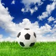 Soccer ball on green grass over dramatic blue sky — Stock Photo