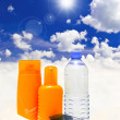 Stock Photo: Sun protection cream, water and sunglasses on sand beach
