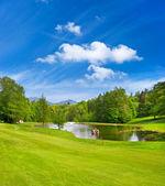 Grünen golfplatz mit blauer himmel — Stockfoto