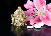 Buddha with stones and lily flower — Stock Photo