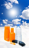 Sun protection cream, water and sunglasses over blue sky — Stock Photo