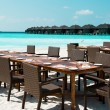 Table and chairs on exotic beach — Stock Photo