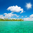 Tropical island beach with cloudy blue sky - Stock Photo