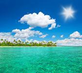 Tropical island beach with cloudy blue sky — Stock Photo