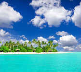 Tropical beach with palm trees over blue cloudy sky — Stock Photo