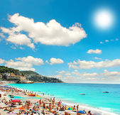 Tourists, sunbeds and umbrellas on summer hot day — Stock Photo
