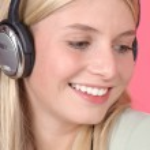 Beautiful blond woman listening music in headphones — Stock Photo