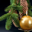 Christmas tree branch with golden burning candle - Stock Photo