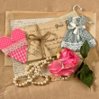 Old post cards, flower, heart and perls necklace - Stock Photo