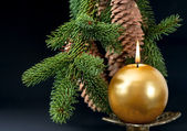 Christmas tree branch with golden burning candle — Stock Photo