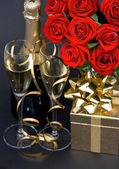 Red roses and champagne on black background — Stock Photo