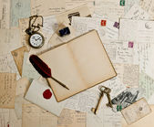 Empty open book, old accessories and post cards — Stock Photo