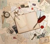 Libro abierto vacía, antiguos accesorios y tarjetas postales — Foto de Stock
