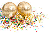 Bolas de natal douradas sobre confetes coloridos — Foto Stock