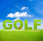 Green golf field with red flag and blue sky — Stock Photo