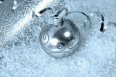 Silver christmas bauble with streamer and snow — Stock Photo