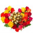 Assorted roses in heart shape with golden ribbon — Stock Photo
