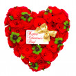 Heart shaped red roses with golden ribbon and white card — Stock Photo